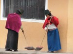 Village women sweep outside a  community building.